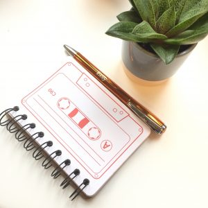 Cassette tape notebook and orange Etsy pen.